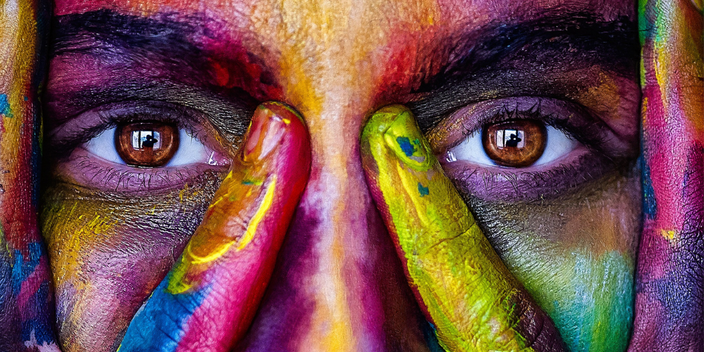 Image of a person's face, looking through their spread fingers. The person is covered in different coloured paint.